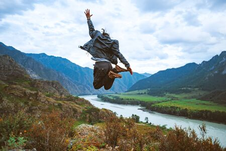 guy jumps on top of a mountain on the background of mountains in a leather jacket