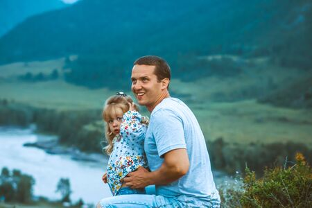 father and daughter on the background of mountains sit and look at nature