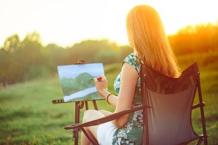 girl draws a picture in nature oil painting by the river Stok Fotoğraf