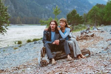 a couple of lovers sit near the river and look at the landscape Фото со стока