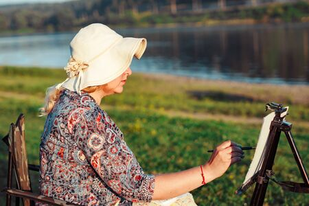 an elderly woman paints a picture in nature oil painting by the river
