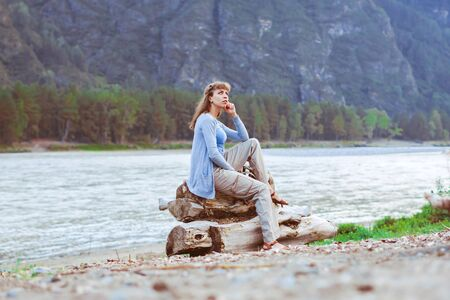 girl sitting by the river on a stone and looking at the landscape