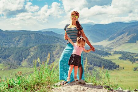 mother and daughter stand on a background of mountains at a height in a Sunny day