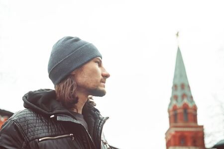a man on the background of the Kremlin in autumn in a hat proudly looks forward