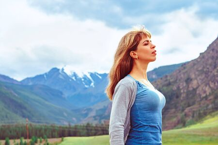 a beautiful girl stands against the background of mountains with white snow Standard-Bild