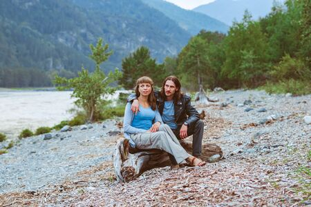 a couple of lovers sit near the river and look at the landscape Standard-Bild