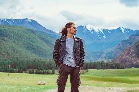 the guy stands against the background of snowy mountains with snow-capped peaks Standard-Bild