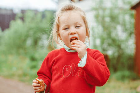 girl on the street eating cookies Standard-Bild