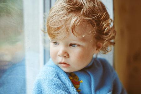a little boy is sitting by the window