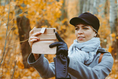 a girl takes photos in the autumn forest