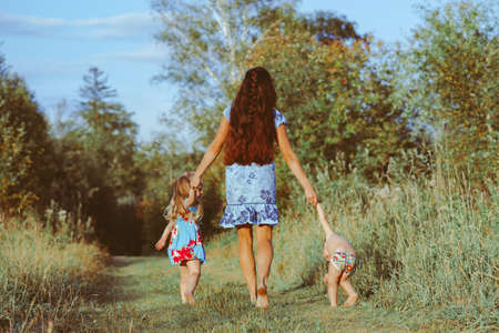 mother walks with children on a forest path
