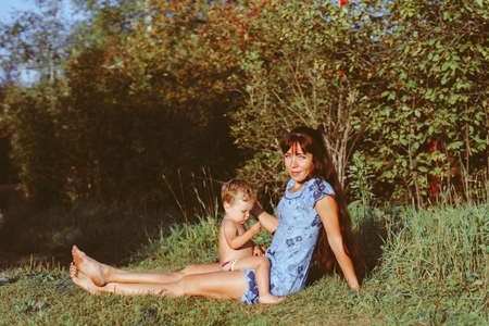 mother sitting on the grass with children
