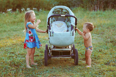 sister plays with her brother in a stroller