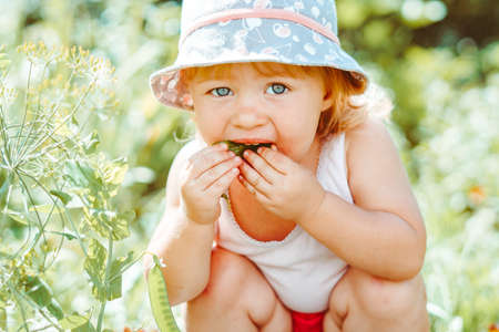 child in the garden with berries