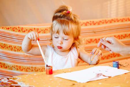 a child draws with gouache in a summer gazebo Standard-Bild