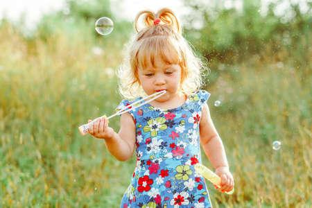 the child blows soap bubbles