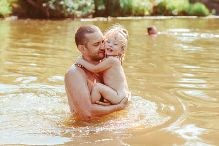 the father with the child in the water