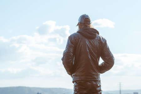 a man in a jacket against a blue sky Standard-Bild