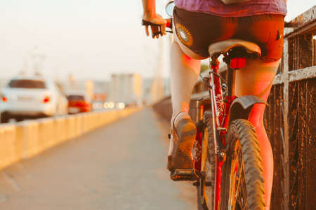 girl rides a bike at sunset Standard-Bild