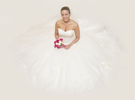 Beautiful portrait of attrtactive young bride sat on floor surrounded by white wedding dress photo