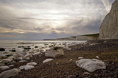 Sunset over white cliffs and rocky beach photo