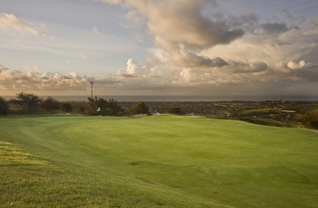 View of golf course with moody sunrise over English landscape photo