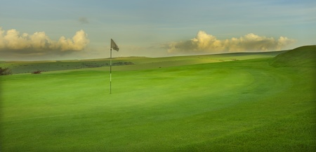 View of golf course with moody sunrise over English landscape