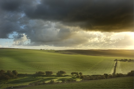 cloudy moody: Stunning sunrise over agricultural landscape in England with ramatic stormy sky Stock Photo