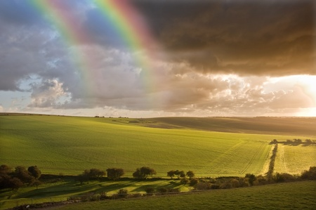 natural moody: Beautiful double rainbow over stormy dramatic sky over English agricultural countryside landscape Stock Photo