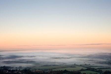 weald: Fog covered English countryside at sunrise looking North from Devils Dyke over the Weald on the South Downs with vibrant colorful sky