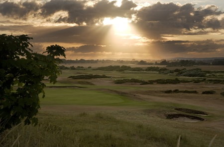 View of sunset across links golf course with sun beams