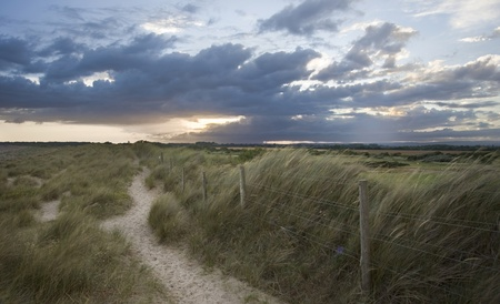 View along dunes path with sotrmy sunset in background photo