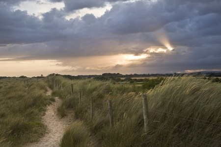 View across sand sunes to countryside with sunbeams through stormy clouds photo