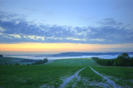 Misty sunrise over fields with low clouds photo