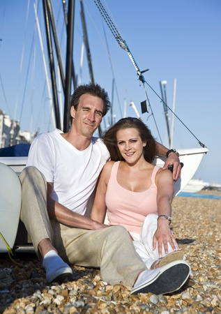 british short hair: Young attractive couple relax on beach at sunset in front of small sailing boat