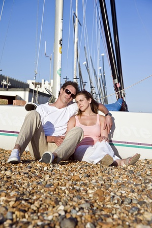 Young attractive couple relax on beach at sunset in front of small sailing boat photo