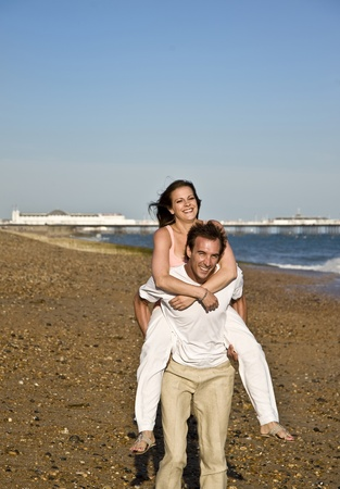 Young attractive couple in love play on beach under beautiful blue sky photo