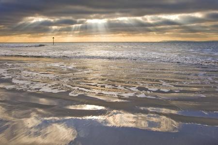 Stunning inspirational sunset image with glowing sun beams photo