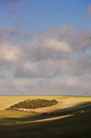 Stunning views across countryside landscape of rolling hills and valleys with sunlight playing across peaks and troughs photo