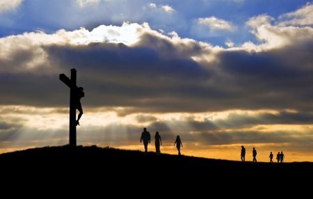 good color: Silhouette of Jesus Christ crucifixion on cross on Good Friday Easter witth people walking up hill towards Jesus