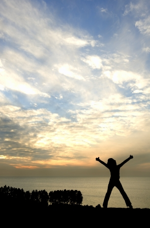 Silhouette of young happy girl looking out to sea with arms stretched in victory pose photo