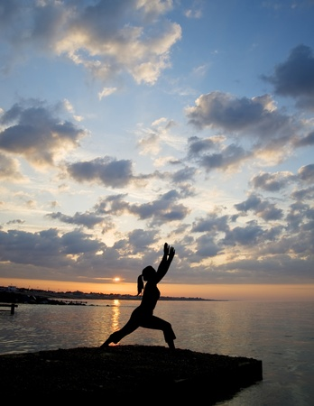 Silhouette of fit young woman doing stretching exercises on pier at sunrise photo