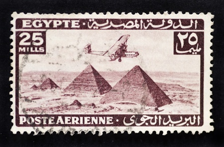 Antique postage stamp showing vintage bi-plane flying over the pyramids in Egypt to represent airmail postage Stock Photo - 8804923