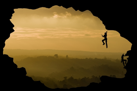 insurmountable: Silhouette of rock climbers concept of achievement