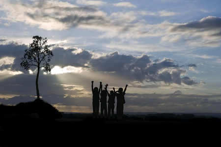 Silhouette of four happy young kids against lovely sunset photo