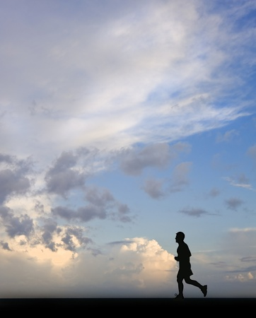 Single man running silhouette against deep blue sky photo