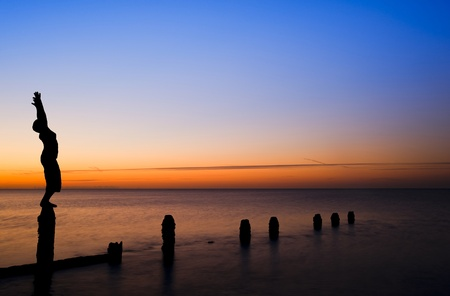 Silhouette of young woman doing exercises on empty beach at sunset photo
