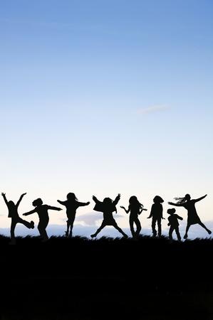 Silhouette der Gruppe von Kindern, die in der Luft gegen vivid sunset Sky jumping Lizenzfreie Bilder