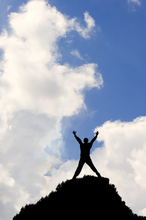 overcoming adversity: Silhouette of concept of achievement or victory man against vivid blue sky and white clouds Stock Photo