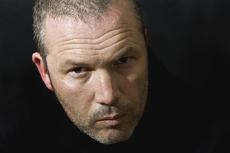 menacing: Dark and moody portrait of serious looking male adult Stock Photo